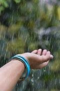 Woman hand with bangles enjoying rain in outdoor Stock Photos
