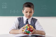 Girl with Rubik cube in a classroom Stock Photos