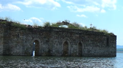 Old christian church under water with metal candlestick on the shore and cross - stock footage