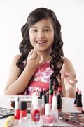Cute girl applying lip gloss Stock Photos