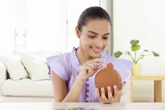 Smiling Teenage Girls Holding a money bank In Her Hand and dropping a coin In Stock Photos