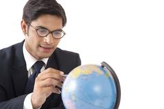 Young professional man locating countries on globe against white background Stock Photos