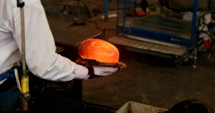 Over the shoulder view of glass blower shaping glob of glass ready to be moulded Stock Footage