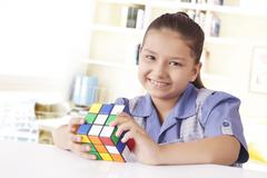 Girl in school uniform playing Rubik's cube Stock Photos