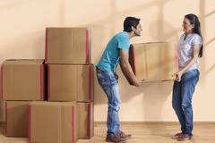 Couple hauling cardboard boxes in new house Stock Photos