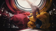 A man opens the door and load the laundry into the washing machine - stock footage