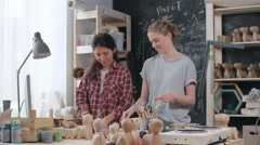 Medium shot of two young female artists talking while making paper mache eco  Stock Footage