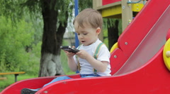 Little boy sitting on a red hill, playground, playing with the phone, smartphone Stock Footage