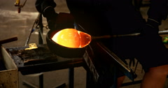 Skilled glass blower shaping and moulding large glob of molten glass Stock Footage