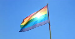 Sun shining through a gay pride flag waving against clear sky - stock footage