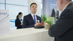 4K Bank worker at service desk taking cash deposit from a customer. Stock Footage