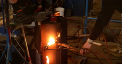 Two men working a glass mould with burners in a busy factory Stock Footage