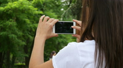 Holding smart phone shooting video for social media - girl back view Stock Footage