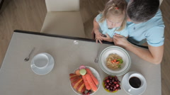 Happy kid girl and woman preparing healthy breakfast together - top view. Mother Stock Footage