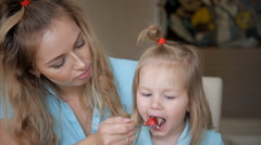 Young mother feeds her young child from a spoon. Oatmeel breakfast with mother Stock Footage
