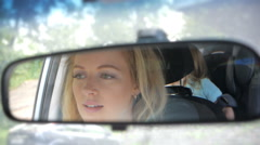 Mother driving a car, having her little baby girl in a child seat Stock Footage