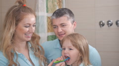 Mother and father teaching little daughter clean teeth - stock footage