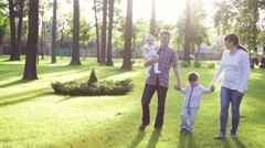 Happy young family spending time together outside in green summer park Stock Footage