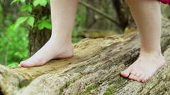 Feet of girl walking across log in forest 4k Stock Footage