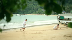 Romantic young couple draw heart shapes in the sand on the beach Stock Footage
