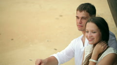 Shipwrecked. Couple in white clothes on a tropical beach sitting near the ship Stock Footage