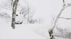Snowboarder in the Backcountry Outdoors Riding and Jumping Down the Ski Hill Stock Footage