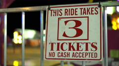 3 tickets to ride sign at carnival with ride spinning in background 4k Stock Footage