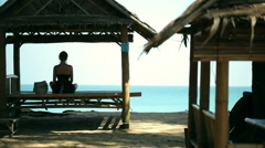 Silhouette young woman practicing yoga in pavilion in front of the beach - stock footage