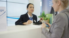 4K Bank worker at service desk taking cash deposit from a customer Stock Footage