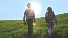 Boy and girl walking in the rays of the bright sun on a green meadow. Stock Footage