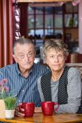 Skeptical Mature Couple in Coffee House Stock Photos