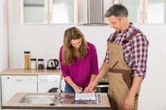 Happy Woman Signing Invoice From Male Plumber In Kitchen - stock photo