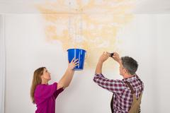 Male Worker Photographing Water Damaged Ceiling While Woman Collecting Water  Stock Photos