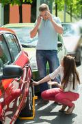 Woman Looking At Man Calling For To Unlock Wheellock Of Illegally Parked Car - stock photo