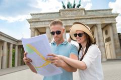 Young Couple Looking At Map In Front Of Brandenburg Gate - stock photo