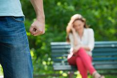 Upset Woman Sitting On Bench After Having Argument At Park - stock photo