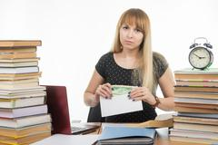 Upset girl student puts money in an envelope to bribe the teacher in the exam - stock photo