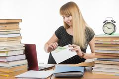The girl puts money in an envelope to bribe the teacher in the exam Stock Photos