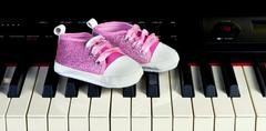 Pink baby shoes on piano key board. Stock Photos