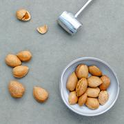 Almonds kernels and whole almonds on concrete background. Whole and chopped a Stock Photos