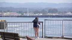 Sexy girl at beach taking pictures of the ocean Stock Footage