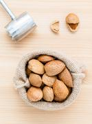 Almonds kernels and whole almonds on wooden background. Whole and chopped alm Stock Photos