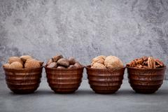 Whole almonds,whole walnuts ,whole hazelnut and pecan nuts in wooden bowl set Stock Photos