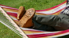 4K.  Foots of man  in yellow buts in hammock  Stock Footage