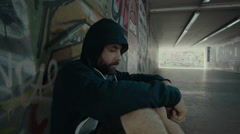 An addicted delirius man leaning against a wall at a city tunnel/underpass. - stock footage