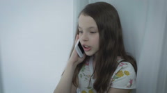 Beautiful little girl emotional talking on smart phone Stock Footage