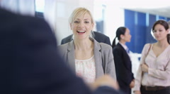 4K Friendly bank worker assisting queue of customers with enquiries Stock Footage