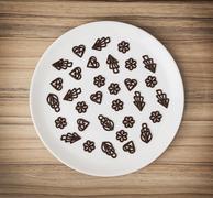 Dark chocolate garnishes in the big plate, symbolic food Stock Photos