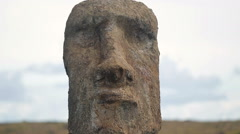 Close-up on Moai statue's face under the cloudy sky Stock Footage