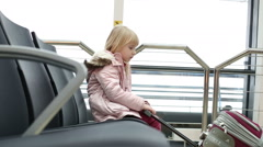Child passenger.  Small blonde girl sitting on a black chair in the airport. Stock Footage